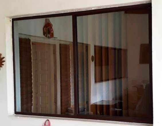 Ventanas corredizas aluminio anodizado bronce y vidrio color bronce.